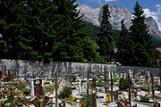 Cemetery in the Dolomites resort town of San Cassiano-St. Kassian in south Tyrol, Italy. South Tyrol is a very religious and traditional country. Life expectancy for south Tyroleans is 85 for females and 80 for males, higher than Italian national averages. According to the 2011 census, there are 505,000 inhabitants in south Tyrol. The weekly walk to Mass and the celebration of religious festivals and processions are part of the culture and tradition in South Tyrol. In almost every house you will find a cross on a corner with consecrated palm branches over there. Also in the stable there are consecrated palm branches to keep away every disaster. South Tyroleans are almost all Catholics and quite conservative.