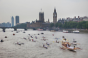 London, UK. Friday 27th July 2012. The London 2012 Olympic Games torch makes it's way up the River Thames on the final day of the torch relay. The pageant, led by the official royal barge, Gloriana passed the Houses of Parliament at Westminster flanked by a flotilla of other rowing boats and vessels.