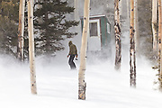 Jeff Wanner, holding a hatchet, battles fierce winds outside the outhouse of the North Pole Hut, in the San Juan Mountains, Colorado.