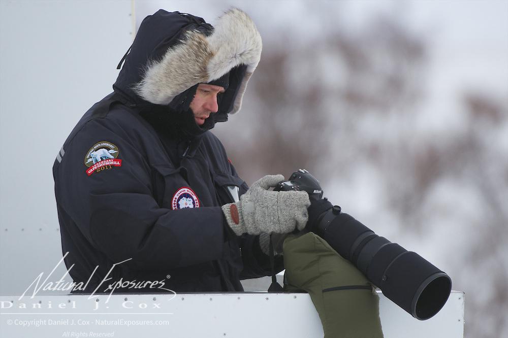 Christian Engel checks his camera gear on the back deck of a Tundra Buggy, Hudson Bay, Manitoba.