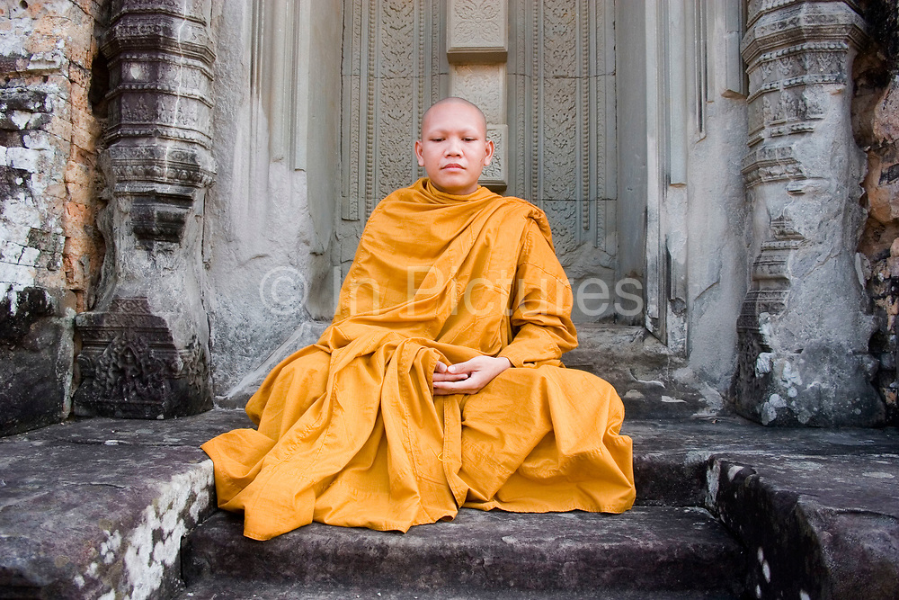 Young Buddhist monk Ronrom (20), sits in a doorway at East Mebon  where he and his colleagues and venerable teachers have come for the day. Based at the nearby Pradaet Pagoda, his learning of Buddhism will last for ten years. Built in 953 for King Rajendravarman's parents, the original temple was surrounded by water so approached by boat. The sandstone towers at the summit are in the Pre Rup style.