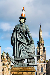 A traffic cone has been added to the statue of Adam Smith on the Royal Mile in Edinburgh Old Town, Scotland, UK
