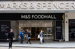 © Licensed to London News Pictures. 26/05/2021. LONDON, UK.  Shoppers pass the exterior of Marks & Spencer's foodhall at the flagship store on Oxford Street.  The company has reported losses of £201.2m and announced plans to recover from the effect of high street store closures lockdowns by shutting stores and increasing online grocery sales. Photo credit: Stephen Chung/LNP