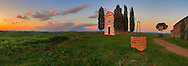 A glorious sunset at the Chapel of Vitaleta in Val d'Orcia, Tuscany, Italy. The Chapel of the Madonna od Vitaleta is a rural small church placed atop a hill in the country side between Pienza and San Quirico d'Orcia. Taken on a early morning at the beginning of April.