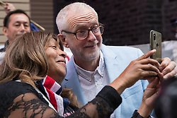 London, UK. 5th July, 2021. A woman poses for a selfie with former Labour Party leader Jeremy Corbyn at a rally organised by Doctors in Unite outside the Department of Health and Social Care. The rally was organised to mark the 73rd birthday of the National Health Service and in protest against the sale of one of the UK's biggest GP practice operators to the US health insurance group Centene Corporation.