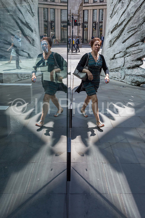 A businesswoman walks past the sculpture entitled City Wing on Threadneedle Street in the City of London, the capitals financial district aka the Square Mile, on 11th July 2019, in London, England. City Wing is by the artist Christopher Le Brun. The ten-metre-tall bronze sculpture is by President of the Royal Academy of Arts, Christopher Le Brun, commissioned by Hammerson in 2009. It is called 'The City Wing' and has been cast by Morris Singer Art Founders, reputedly the oldest fine art foundry in the world.