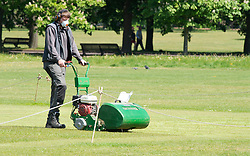 ©Licensed to London News Pictures 06/05/2020  <br /> Greenwich, UK. A groundsman cutting the cricket field. People out and about in Greenwich park, Greenwich, London exercising and enjoying the warm sunny weather.  Photo credit:Grant Falvey/LNP