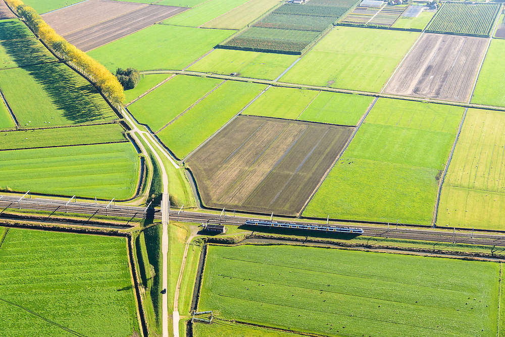 Nederland, Gelderland, Meteren, 24-10-2013; sprinter onderweg van Utrecht naar Den Bosch. Het viaduct voert het landweggetje (de Markkade) over de spoorlijn en vervangt de overweg.<br /> Local train crosses country road, overpass replaces level crossing.<br /> luchtfoto (toeslag op standaard tarieven);<br /> aerial photo (additional fee required);<br /> copyright foto/photo Siebe Swart.
