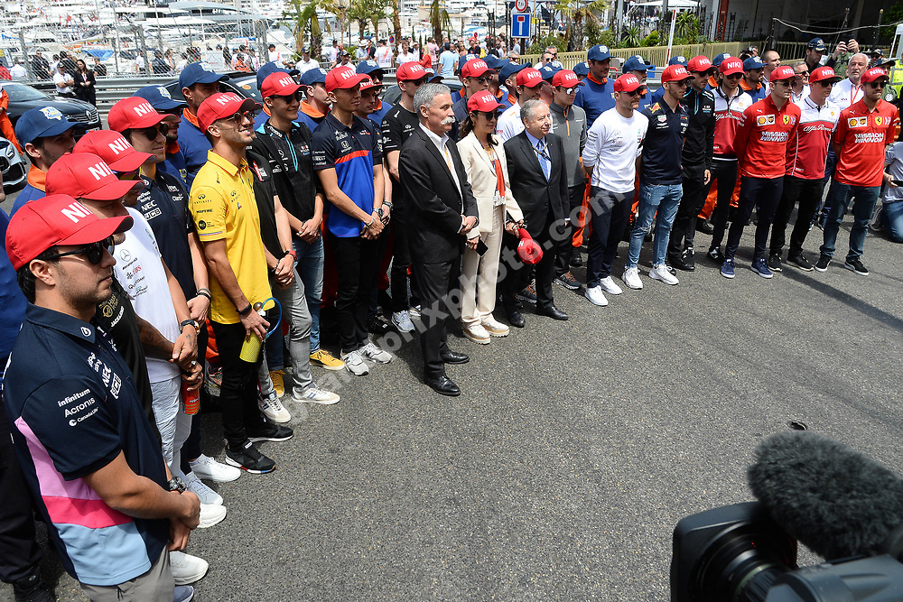 All drivers, Chase Carey, Jean Todt and Michelle Yeoh with red caps in memory of Niki Lauda before the 2019 Monaco Grand Prix. Photo: Grand Prix Photo