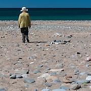 Woman in hat walking on beach, Isle of Man.