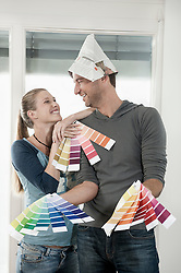 Couple choosing colour samples and smiling, Bavaria, Germany