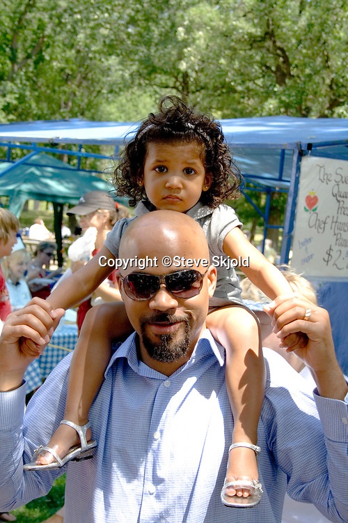 Man with daughter on shoulder enjoy celebration. Svenskarnas Dag Swedish Heritage Day Minnehaha Park Minneapolis Minnesota USA