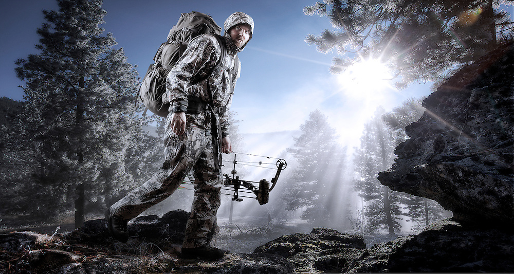 A composite image of an archery hunter hiking along a rock outcropping high in the mountains during a cold fall morning while the sun is starting to cut through the misty fog.