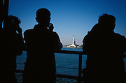 Back of tourists on a boat looking at the Statue of Liberty