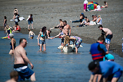 © Licensed to London News Pictures. 19/07/2016. Aberystwyth, Wales, UK. People enjoying themselves at the seaside in Aberystwyth making the most of the hottest day of the year so far. The temperature is set to reach the mid 30's centigrade in parts of the south east of the UK today, before heavy thunderstorms sweep in on Wednesday.  Photo credit: Keith Morris/LNP