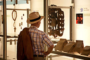 The British Museum, London. Visitor looks closely at a display from Africa.