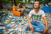 """12 DECEMBER 2012 - BANGKOK, THAILAND:  Demolition workers relax at the end of their shift in """"Washington Square"""" a notorious entertainment district off Sukhumvit Soi 22 in Bangkok. Demolition workers on many projects in Thailand live on their job site tearing down the building and recycling what can recycled as they do so until the site is no longer inhabitable. They sleep on the floors in the buildings or sometimes in tents, cooking on gas or charcoal stoves working from morning till dark. Sometimes families live and work together, other times just men. Washington Square was one of Bangkok's oldest red light districts. It was closed early 2012 and is being torn down to make way for redevelopment.    PHOTO BY JACK KURTZ"""