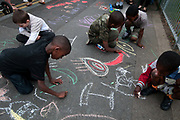 Clarence Road Hackney. Street tea party one week after the riots. A group of young children draw with chalk sticks on the street.
