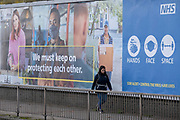 A south Londoner walks past an NHS (National Health Service) ad asking the publc to protect each other with face coverings on Queenstown Road in Battersea, during the second lockdown of the UK's Coronavirus pandemic, when all but essential retailers and businesses remain shut according to the government's restriction rules, on 13th November 2020, in London, England.