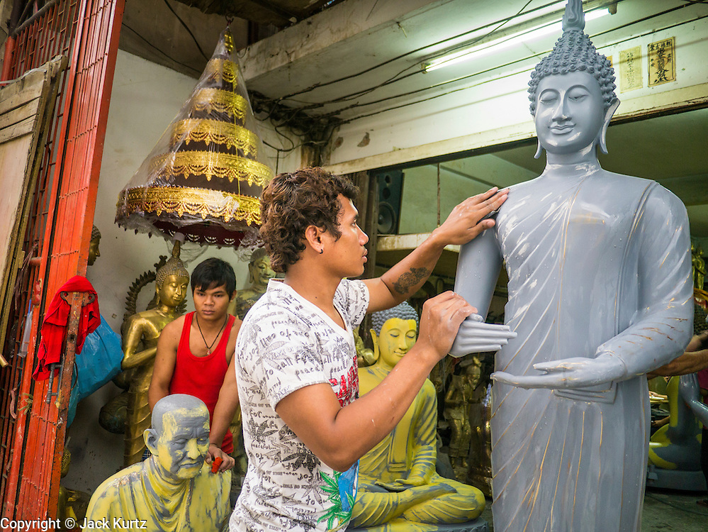 """12 NOVEMBER 2012 - BANGKOK, THAILAND:   Workers finish a statue of the Buddha at a shop on Bamrung Muang Street in Bangkok. Thanon Bamrung Muang (Thanon is Thai for Road or Street) is Bangkok's """"Street of Many Buddhas."""" Like many ancient cities, Bangkok was once a city of artisan's neighborhoods and Bamrung Muang Road, near Bangkok's present day city hall, was once the street where all the country's Buddha statues were made. Now they made in factories on the edge of Bangkok, but Bamrung Muang Road is still where the statues are sold. Once an elephant trail, it was one of the first streets paved in Bangkok. It is the largest center of Buddhist supplies in Thailand. Not just statues but also monk's robes, candles, alms bowls, and pre-configured alms baskets are for sale along both sides of the street.    PHOTO BY JACK KURTZ"""