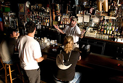 10 Sept 2005. New Orleans, Louisiana.  Hurricane Katrina aftermath.<br /> Jim Monaghan, the barman at Molly's  bar on Decatur Street talks with customers. The famous French Quarter bar remained open throughout the days following the storm.<br /> Photo; ©Charlie Varley/varleypix.com