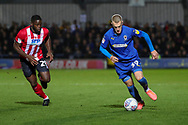 AFC Wimbledon striker Joe Pigott (39) dribbling away from Lincoln City attacker John Akinde (29) during the EFL Sky Bet League 1 match between AFC Wimbledon and Lincoln City at the Cherry Red Records Stadium, Kingston, England on 2 November 2019.
