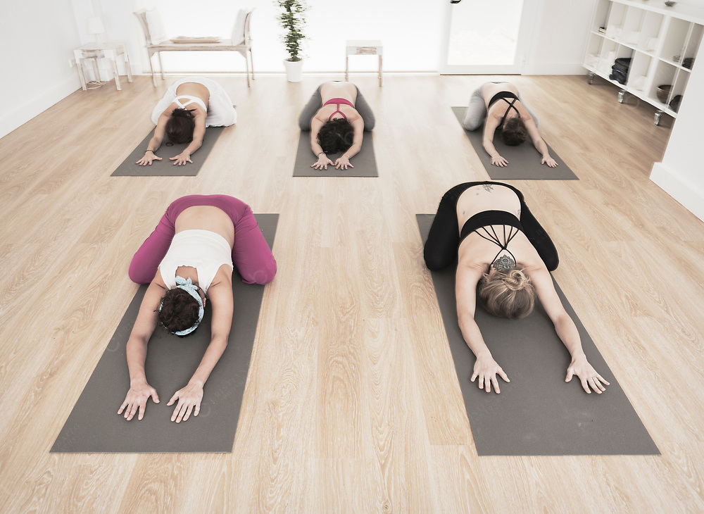 Group of pregnant woman in yoga class doing child pose