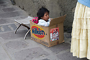 La Paz, Bolivia. Baby in a box, by the side of her working mother.