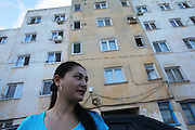 19 year old Isabella Baboi outside her home in Alexandria, where she lives with her mother and sister. Her mother Ilana looks from the 3rd floor window. Isobella was expelled from France on 25th September by the police authorities for stealing chewing gum and face-cream. She declared herself as being homeless and returned to Romania with just the clothes she was wearing at the time of her arrest. She will return to Paris suburbs very soon, where her father and cousins are living. Alexandria, Romania..Roma Gypsies left India 1000 years ago. Often nomadic. A collection of tribes with their own languages and culture, pushed by the Ottoman empire towards Europe, used and sold as mercenaries, slaves, prostitutes. They endured 500 years of slavery until mid 19th century. A million were killed in the holocaust. Hundreds of thousands exiled and refugees from kosovo. Many Eastern Europe Roma come to the west seeking a better life. They are shunned, marginalized, excluded. Both indigenous and foriegn Roma, whether European citizens or not, lack the opportunities of others, living on the periphery, in the brunt of racism, often deported back to their countries of origin.
