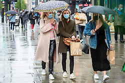 © Licensed to London News Pictures. 21/05/2021. LONDON, UK. People shopping in the rain in Oxford Street.  The Office for National Statistics (ONS) has reported that retail sales in April were 10% more than pre-pandemic levels, with sales of clothing up by 70% compared to March.  It has been suggested that the increase is evidence of the pent-up demand as non-essential shops  reopened in England on 12 April.  Photo credit: Stephen Chung/LNP
