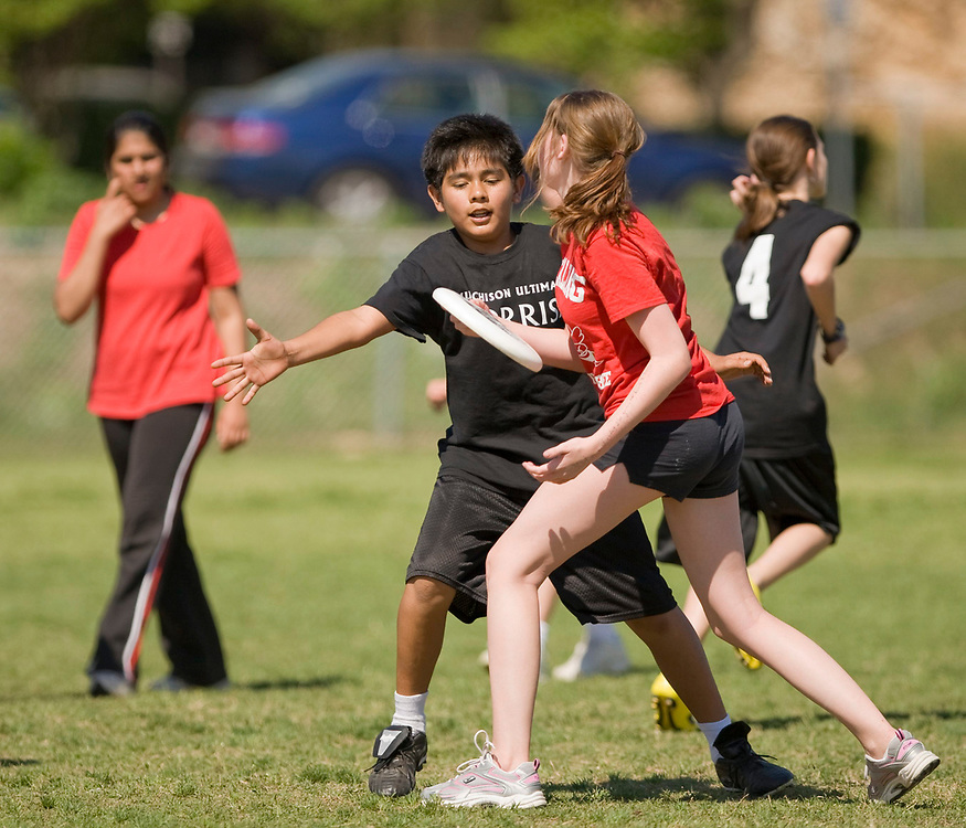 Austin, TX: April 7, 2008: Middle school students from Murchison (black shirts) and Kealing (red shirts) play a competitive game of Ultimate on a spring Saturday afternoon.  Each team starts seven players and uses a flying disc weighing 175 grams in competition.  ©Bob Daemmrich