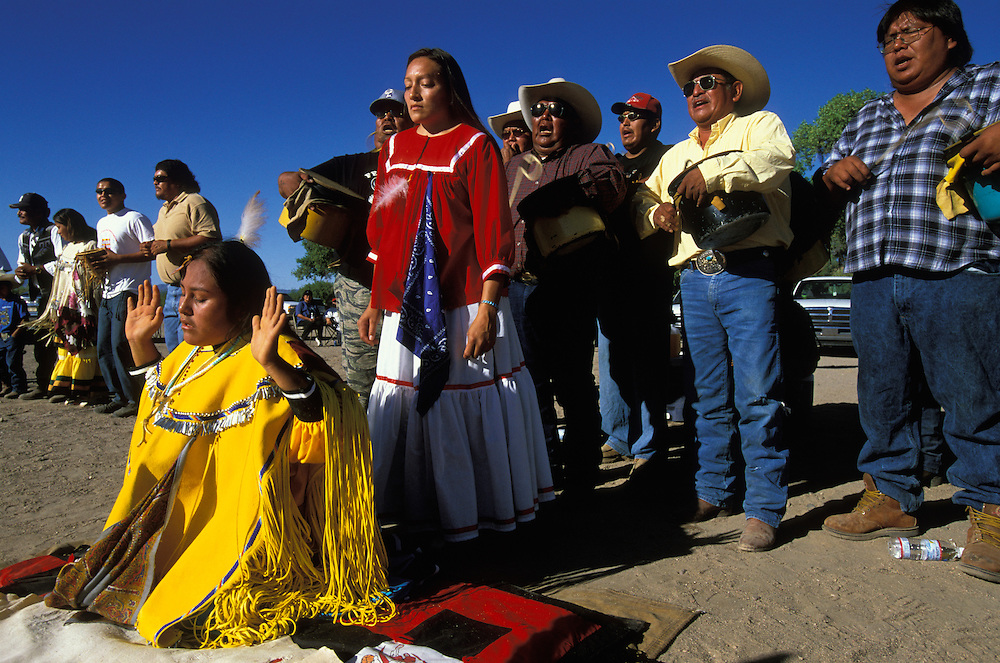 An Apache girl dressed in buckskin clothes dances in a kneeling positon at her Sunrise Dance, a first menstruation rite, the San Carlos Apache Reservation, Arizona, USA. During the ceremony the girl 'becomes' Changing Woman, the mythical founder of the Apache Tribe, and this part of the ceremony is an enactment of when Changing Woman was impregnated by the sun and gave birth to a son.  Behind the girl stands her godmother and behind her the medicine man (third from right) and his assistants sing and beat their drums.