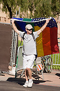 15 NOVEMBER 2008 -- PHOENIX, AZ: A man carrying the gay rights flag crosses a Phoenix street Saturday. About 1,500 people, gay and straight, participated in a rally at the Phoenix, AZ, city hall to protest the passage of Proposition 102 in Arizona and Proposition 8 in California on November 4. In both states the propositions essentially defined marriage as between a man and woman and banned same sex marriages. The protest in Phoenix was one of several held across the United States Saturday. Photo by Jack Kurtz / ZUMA Press