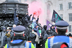 "© Licensed to London News Pictures. 17/03/2018. LONDON, UK. Anti-fascists light flares at Piccadilly Circus chant as people take part in a ""March against Racism"", walking from Portland Place to Downing Street, calling for a united movement for everyone against all forms of racism.  Photo credit: Stephen Chung/LNP"