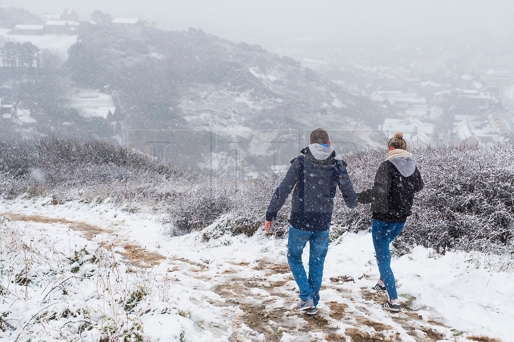 © Licensed to London News Pictures. 10/12/2017. Aberystwyth, UK. A couple hold hands while watching the first snow of the winter at Aberystwyth on the Welsh coast, as the wintry conditions spread of much of the middle of the UK.  People are out  walking on Constitution Hill overlooking the town, making the most of the snowy scenes .Photo credit: Keith Morris/LNP