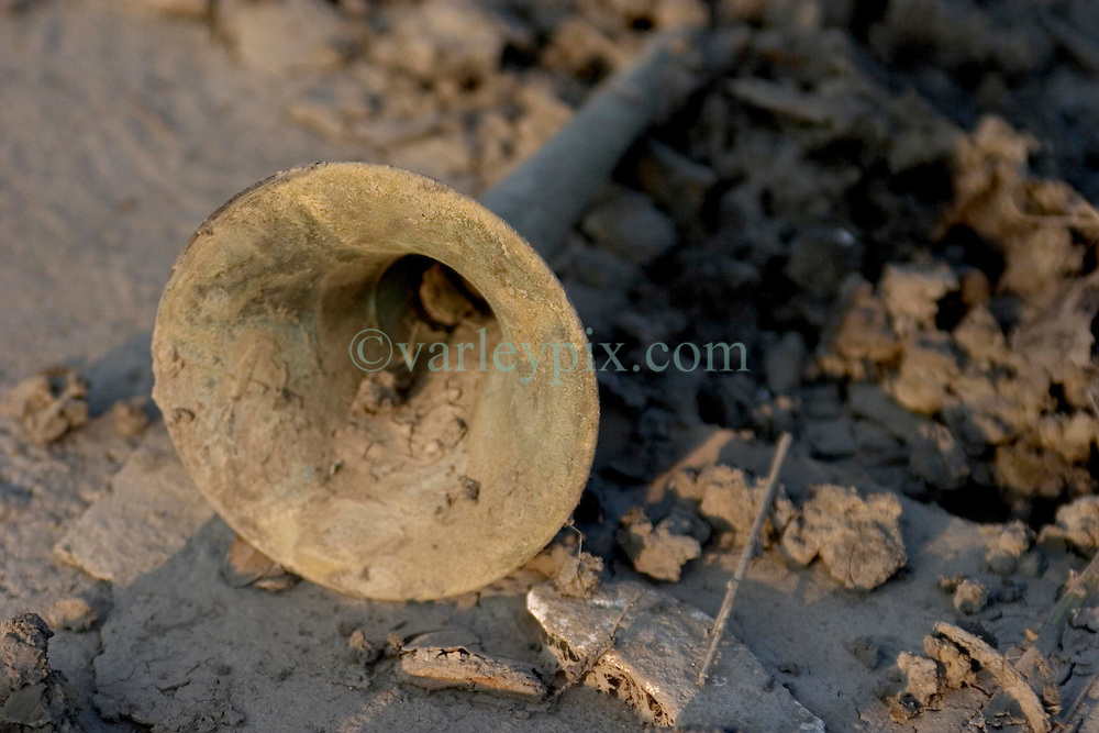30 Sept, 2005.  New Orleans, Louisiana. Lower 9th ward. Hurricane Katrina aftermath. <br />  The remnants of the lives of ordinary folks, now covered in mud as the flood waters recede. All that remains of a trumpet laying in the muck.<br /> Photo; ©Charlie Varley/varleypix.com
