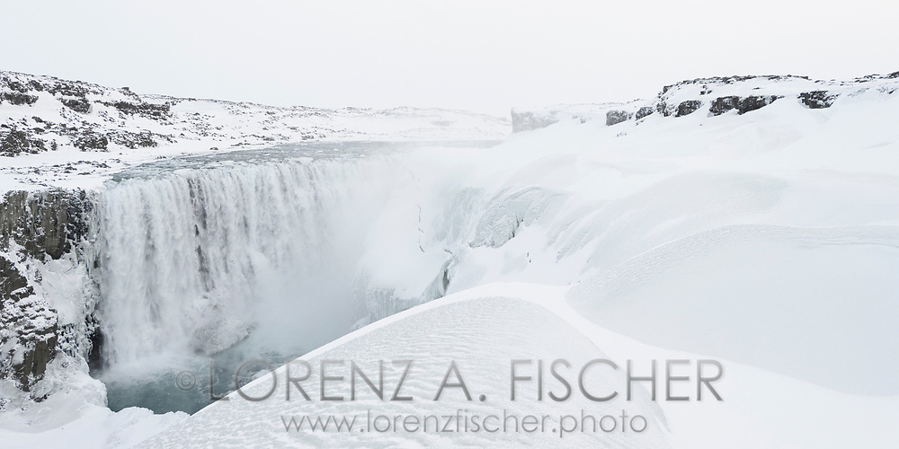 The waterfall Dettifoss in a frozen exposure on a white and cloudy afternoon in wintertime, Iceland