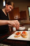 USA, Oregon, Eugene, young woman putting basil on the bruschetta. MR