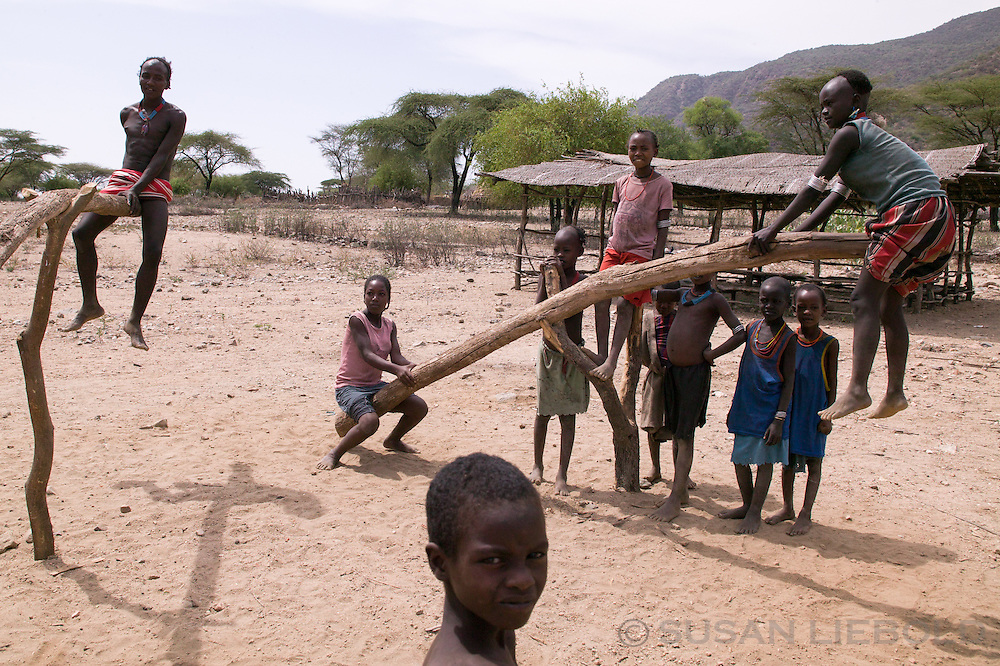 Children playing on seesaws made from tree branches in Southern Ethiopia.