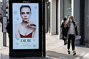 A young woman walks with her phone past an ad for Dior jewellery during the second lockdown of the UK's Coronavirus pandemic, when all but essential retailers and businesses remain shut according to the government's restriction rules, on 13th November 2020, in London, England.