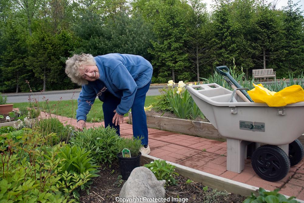 Older woman tending her raised flower bed