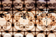 View on a village through a cast iron window grid, Draa Valley, Morocco.