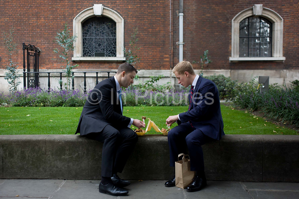 Two businessmen eat takeaway lunches in St Botolph-without-Bishopsgate churchyard. Facing each other on a low wall that borders the grounds of this historic religious site, the men talk and concentrate on forking their food during their hour off. The original Saxon church, the foundations of which were discovered when the present church was erected, is first mentioned as 'Sancti Botolfi Extra Bishopesgate' in 1212. St. Botolph without Bishopsgate may have survived the Great Fire of London unscathed, and only lost one window in the Second World War, but on 24 April 1993 was one of the many buildings to be damaged by an IRA bomb.