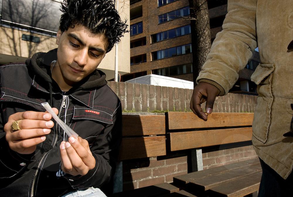 Nederland Rotterdam 12 maart 2007  20070312..Minderjarige allochtone jongen draait blowtje in de openbare buitenruimte.Foto David Rozing