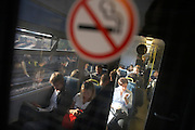 Commuters and no smoking sign on a carriage travelling into London between Denmark Hill and London Bridge stations