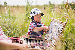 Little boy playing with basket in the countryside, Bavaria, Germany