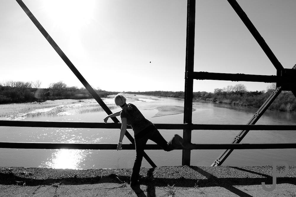 Kay Pratt throwing a rock off a bridge over the Cimarron River in central Oklahoma