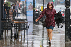 © Licensed to London News Pictures. 25/07/2021. London, UK. A woman is caught out in a heavy downpour in north London., after the recent heatwave.  According to The Met Office, torrential thunderstorms are expected in the capital. Photo credit: Dinendra Haria/LNP
