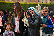 A family join 2000 Goules who took part in the Zombie Walk, 8th October 2016, Paris, France. The walk went from Place de la Republique and finished at Place des Vosges. The event, an apocalyptic parade through Paris's historic downtown. Zombie walks as annual traditions are now relatively common in large cities, especially in North America.