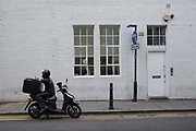 A stationary deliveroo motorcyclist looking at his mobile phone near Hoxton Square on 5th August 2016 in London, United Kingdom. Hoxton Square is a garden square situated in Hoxton in the London Borough of Hackney, in Londons East End. Laid out in 1683, it is thought to be one of the oldest squares in London. From the series Our Small World, an observation of our mobile phone obsessions